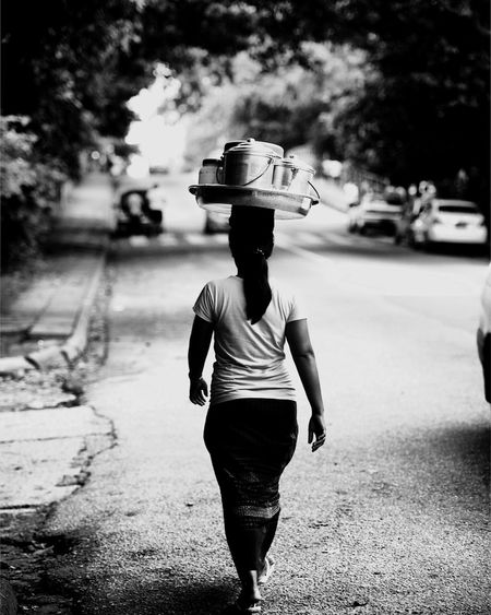 Rear View Of Woman Carrying Containers On Head While Walking On Road