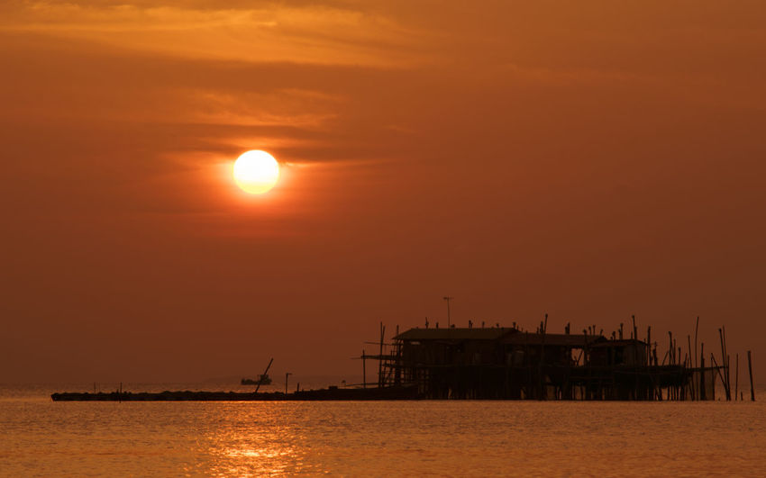 Silhouette built structure in sea against sky during sunset