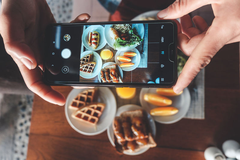 High angle view of person photographing food on table