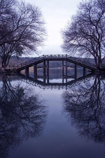 Bridge over river amidst bare trees against sky