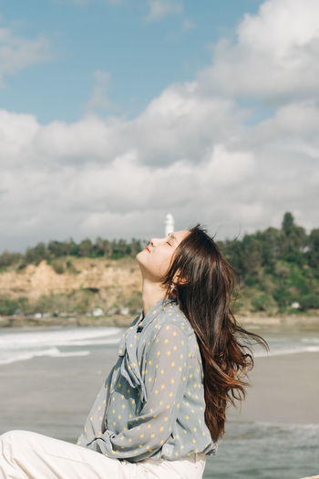 Side view of woman sitting against sky during sunny day