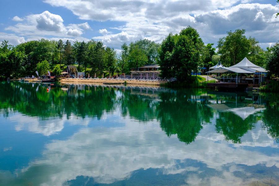 Niedernberg Architecture Beauty In Nature Blue Built Structure Cloud Cloud - Sky Cloudy Day Green Color Growth Idyllic Lake Nature No People Outdoors Reflection Scenics Sky Standing Water Tranquil Scene Tranquility Tree Water
