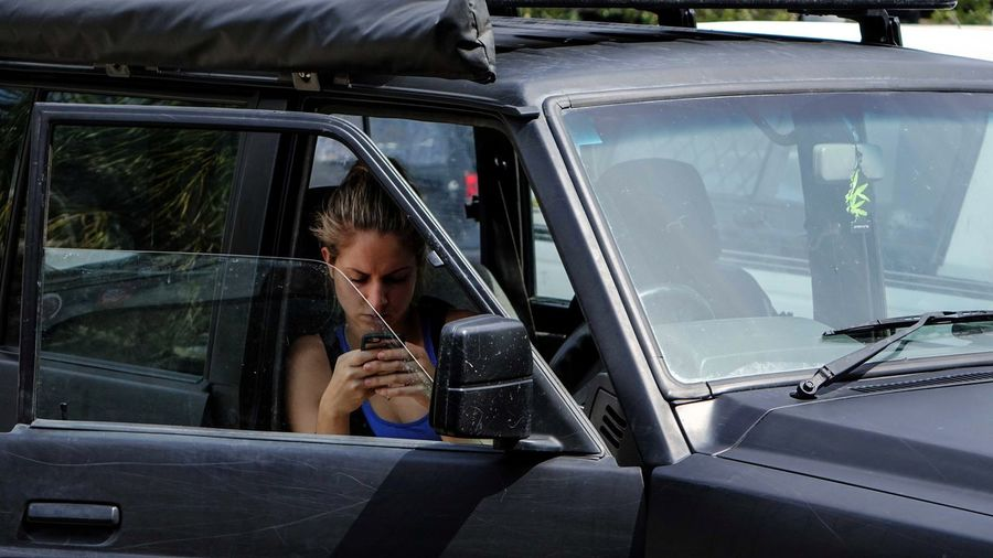 Young woman using mobile phone while sitting in car
