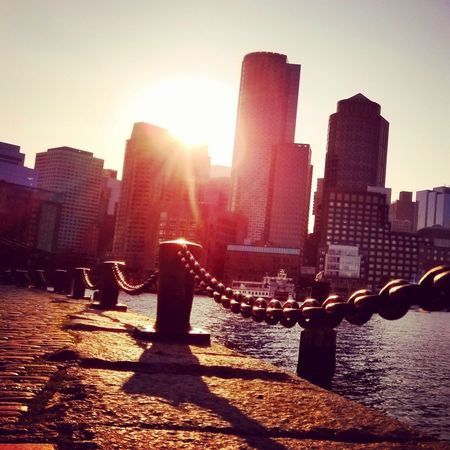 Good evening. Architecture Skyscraper Built Structure Building Exterior City Sunlight Lens Flare Sunset Cityscape Boston New England  City Life Sky Urban Skyline No People Modern Day Clear Sky Water