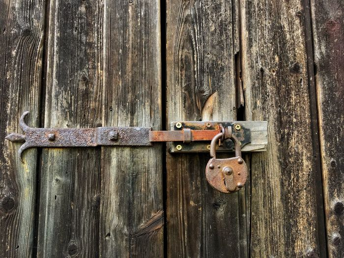 Old door lock on a wooden door Door Safety Wood - Material Closed Metal Security Protection Textured  Lock Latch Close-up Padlock No People Outdoors Rusty Hanging Key Backgrounds Day Old Old-fashioned Old Door Locks Locker Wooden Door