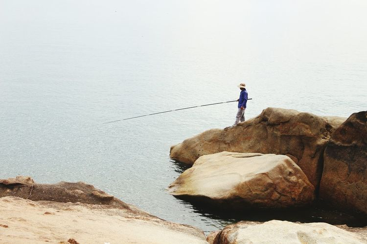Side view of man fishing in sea