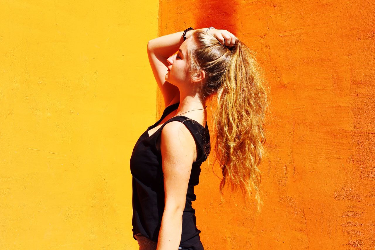 Side view of young woman with hand in hair standing against orange wall