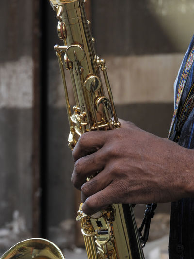 Cropped Hand Of Musician Playing Saxophone Outdoors