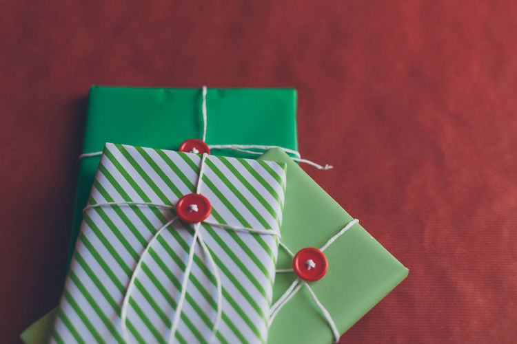 Celebration Christmas Holiday Art And Craft Close-up Directly Above Emotion Focus On Foreground Gift Green Color High Angle View Indoors  No People Paper Pattern Red Ribbon Selective Focus Still Life Straight Pin Striped Table White Color