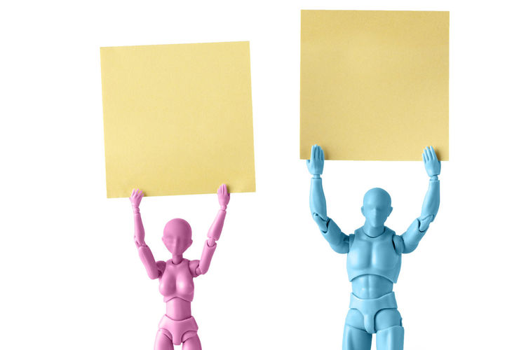 Figurines Holding Blank Papers Against White Background