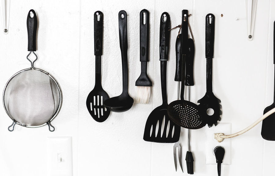 Utensils on the Wall - Closeup of cooking utensils hanging from nails on a kitchen wall Fork Wall Close Up Closeup Cookery Cooking Equipment Cooking Utensil Food Preparation Hanging Household Items Household Objects Indoors  Indoors  Interior Kitchen Kitchen Utensil Ladle No People Odd Organization Plastic Spatula Strainer Strange White Background