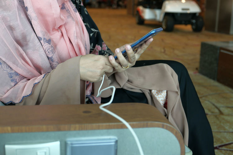 Close up of women hand charging smart phone at airport