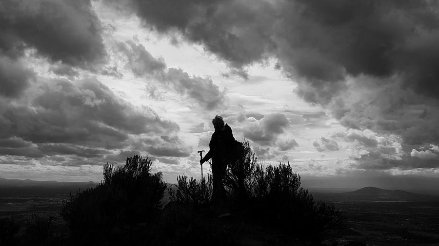 Silhouette man standing by tree against sky