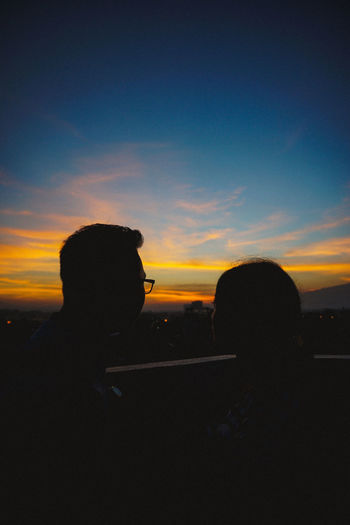 Silhouette couple against sky during sunset