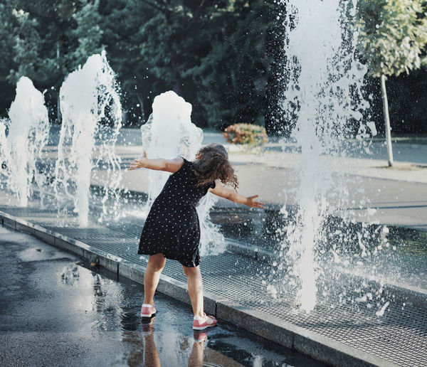 Full Length Of Girl Playing In Water Fountain At Town Square