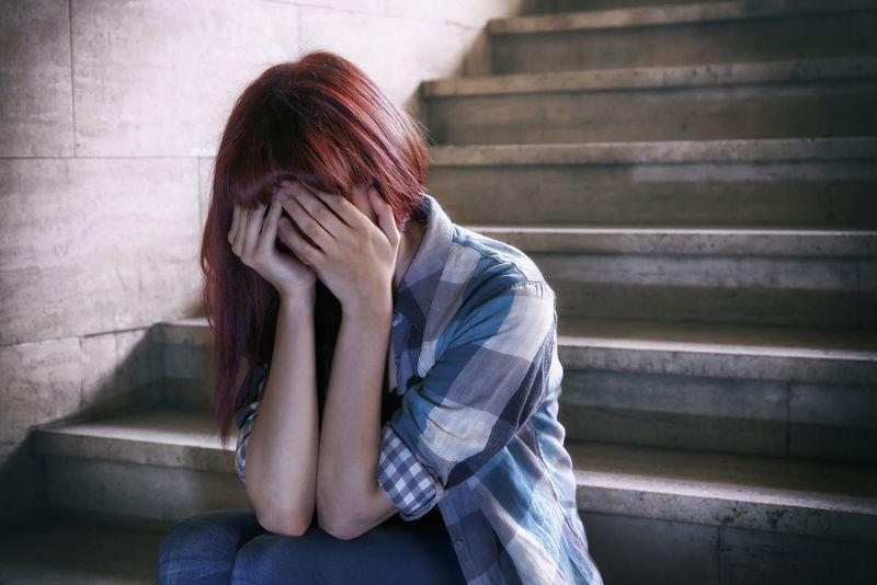 Girl in adolescent crisis sitting on the steps of a basement, covers her face with her hands. A natural light penetrates from above. Basement Casual Clothing Covered Crisis Crying Depressed Desperate Fleesensee Girl Her Face Hidden Hiding Lifestyles Long Hair Psychological Red Hair Reflects Sad Sitting Stairs Teenager Young Woman