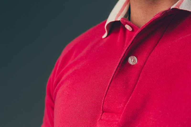 Close up of a young adult caucasian male wearing a red polo shirt Shirt Midsection Front View Side View One Person Red Casual Clothing Real People Indoors  Lifestyles Close-up Clothing Adult Fashion Human Body Part Human Arm Studio Shot Men Menswear Mensfashion Menstyle Polo Shirt  T-shirt Advertisement Standing Fashion Model Textile Texture Confidence  Copy Space Chest Design Caucasian Freshness