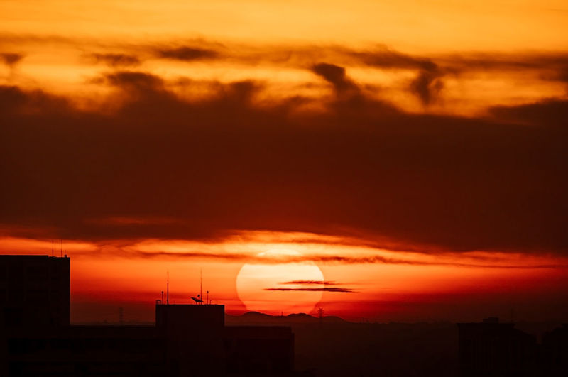Silhouette buildings against dramatic sky during sunset
