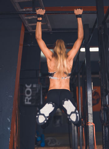 Exercising Indoor Activities Musculation  Squat Blonde Exercising Cross Training Crossfit Crossfit Girl Energy Gym Health Club Kettlebell  Kipping Lifestyles Muscular Build One Person People Real People Rear View Sport Clothing Stretching Strong Woman Training Weightlifting Workout