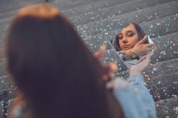 Woman holding mirror on staircase with multi colored confetti