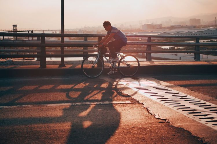 Rider Bicycle Railing Transportation Bridge - Man Made Structure Sunlight Mode Of Transport Full Length Land Vehicle Sunset Outdoors Real People Cycling Riding One Person Shadow City Lifestyles