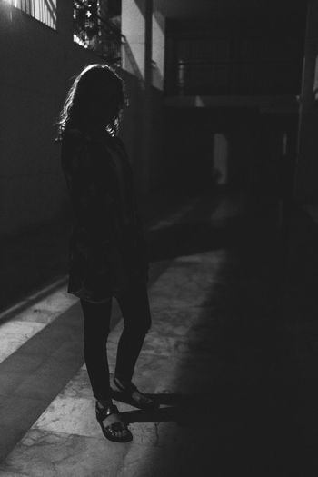 Side view of woman walking on footpath at night