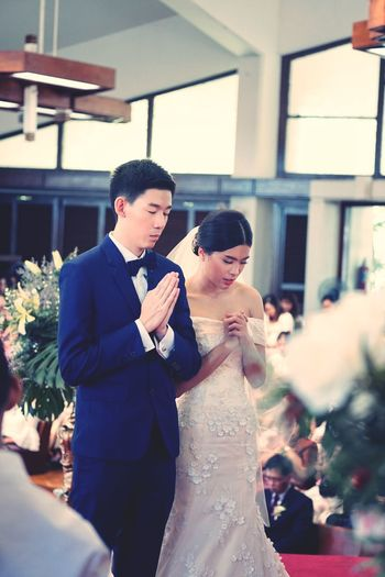 Young Couple Standing In Church During Wedding Ceremony
