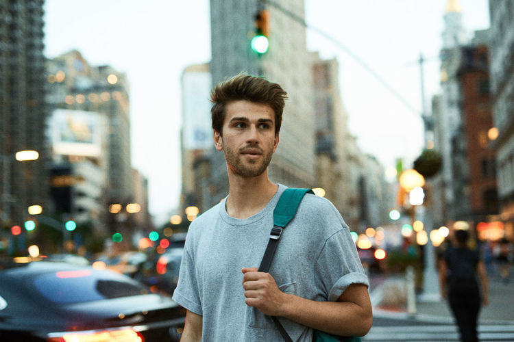 Portrait of young man standing on city street at night