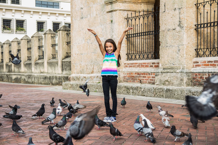 Animal Animal Themes Animal Wildlife Animals In The Wild Architecture Bird Building Exterior Built Structure City Day Flock Of Birds Flying Front View Full Length Group Of Animals Large Group Of Animals One Person Outdoors Pigeon Smiling Vertebrate Young Adult