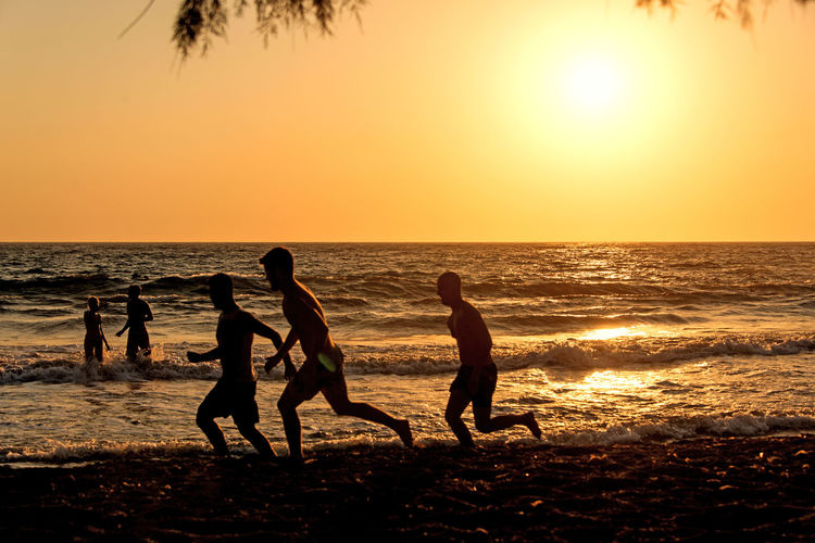People playing, swimming in the waves in the island of Patmos, Greece in summer time Beach Beauty In Nature Group Of People Horizon Horizon Over Water Land Leisure Activity Lifestyles Men Motion Nature Outdoors Real People Scenics - Nature Sea Silhouette Sky Sport Sun Sunset Water