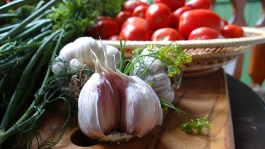 Close-Up Of Garlic Bulbs And Herbs By Tomatoes On Table