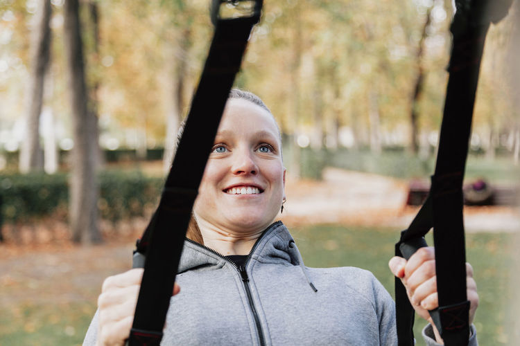 Close-up of smiling woman exercising at park