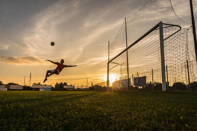 Full length of man playing soccer against sky during sunset