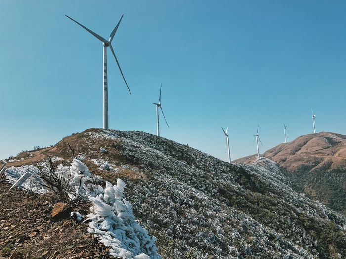 Low angle view of wind turbines on land