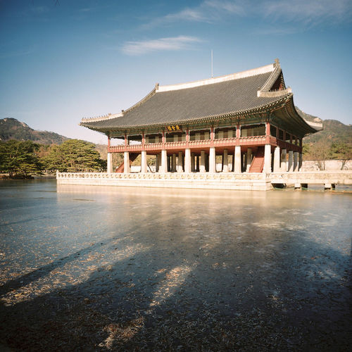 On a wintry morning at Gyeongbokgung Palace in Seoul, Gyeonghoeru Pavilion sits surrounded by a frozen lake. Appreciation Frozen Gyeongbokgung Gyeonghoeru Ice Joseon Royal Banquet Hall Travel Winter Architecture Building Exterior Built Structure Cultural Day Heritage Historic Nature No People Outdoors Palace Shadows Sky Tourism Tree Water