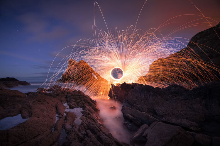 Person spinning burning wire wool at beach against sky