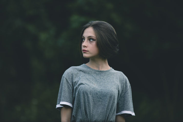 Beautiful young woman looking away against trees