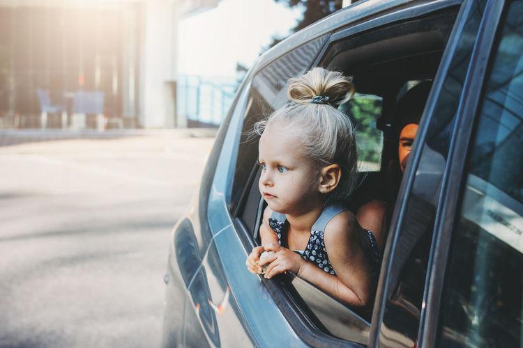 Portrait of boy looking through car window