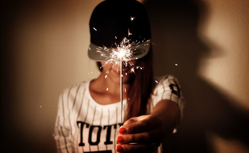 Woman holding sparkler indoors