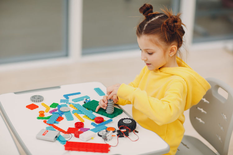 Girl with toys on table