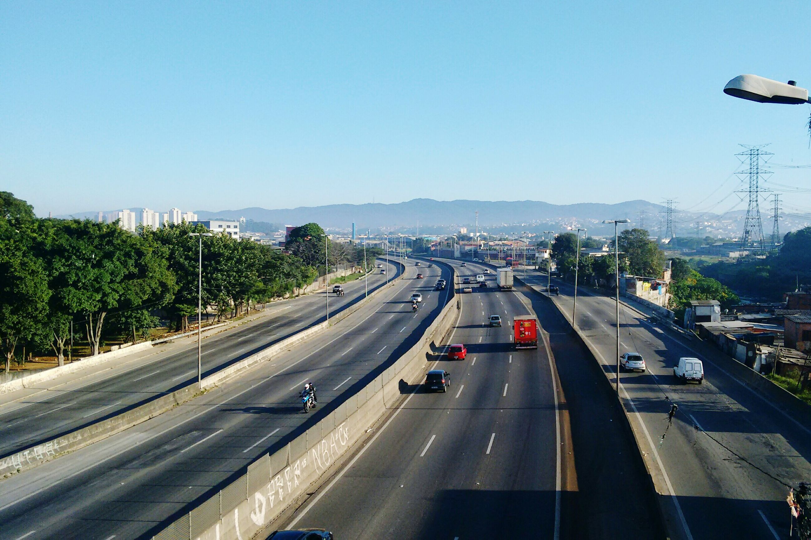 transportation, clear sky, mode of transport, road, car, land vehicle, road marking, on the move, the way forward, copy space, diminishing perspective, high angle view, highway, travel, blue, traffic, tree, vanishing point, street, journey