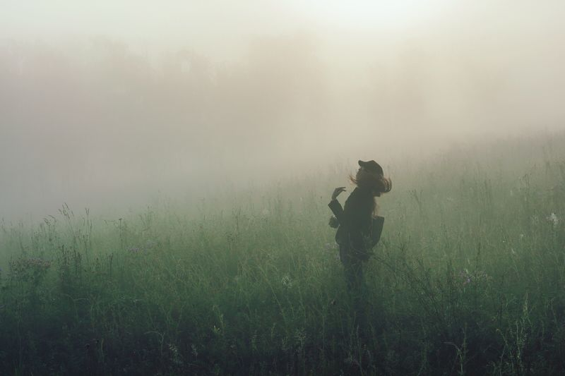 Woman standing on grassy field during foggy weather