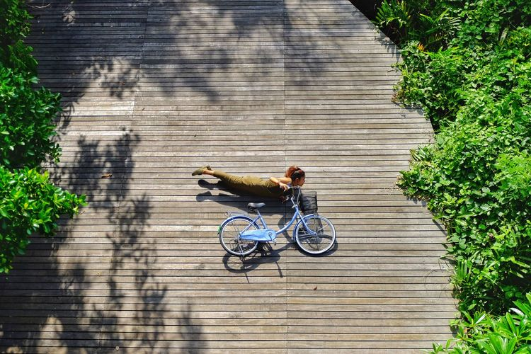 High angle view of woman fallen with bicycle on floorboard during sunny day
