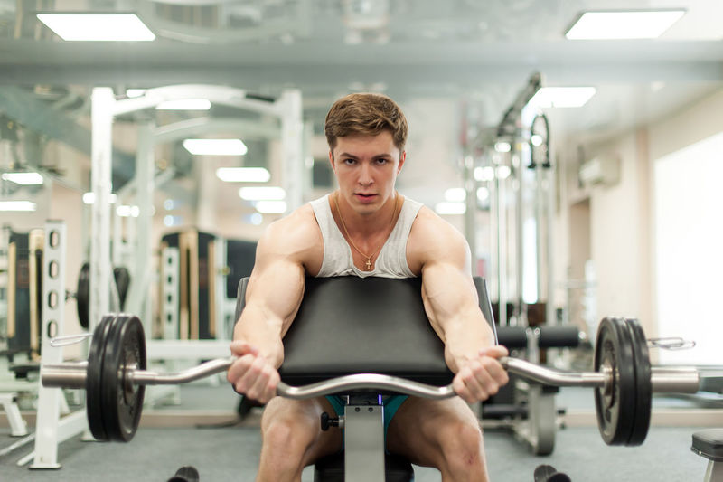 Portrait Of Young Man Exercising In Gym