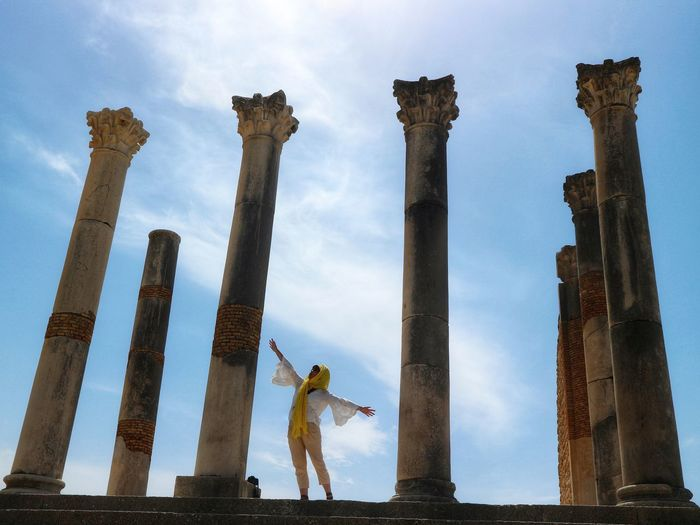 Woman with arms outstretched standing amidst columns of old ruins
