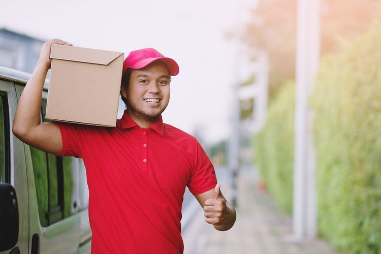 Portrait of smiling delivery person wearing cap standing with cardboard outdoors