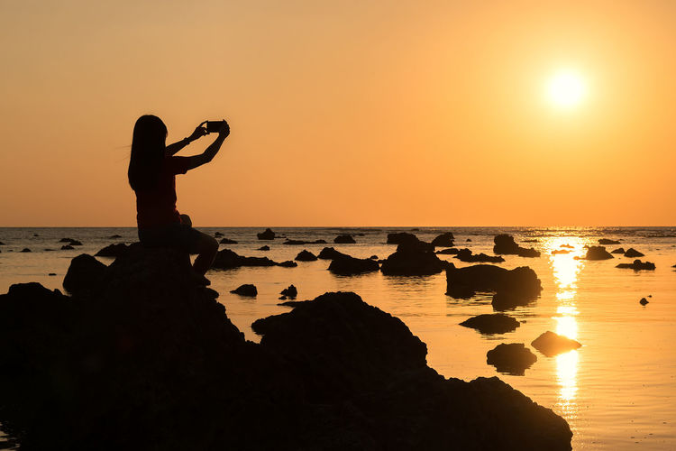 Silhouette Woman Photographing While Sitting On Rock At Beach Against Sky During Sunset
