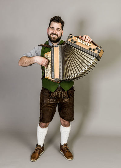 Musician Costume Leather Trousers Tradition Traditional Austria Green Pose Accordion Man Young Shorts Friendly Proud Happy Play Music Fun Joy Single One Background Copy Space Studio Entertainment Mountains Shirt STAND Hobby Leisure Cool Front View Portrait Full Length Looking At Camera Studio Shot One Person Indoors  Smiling Young Adult Holding White Background Casual Clothing Standing Young Men Arts Culture And Entertainment Beard Mid Adult Men