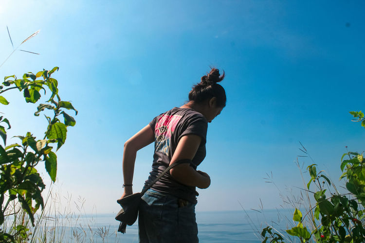 Woman standing by plants against blue sky