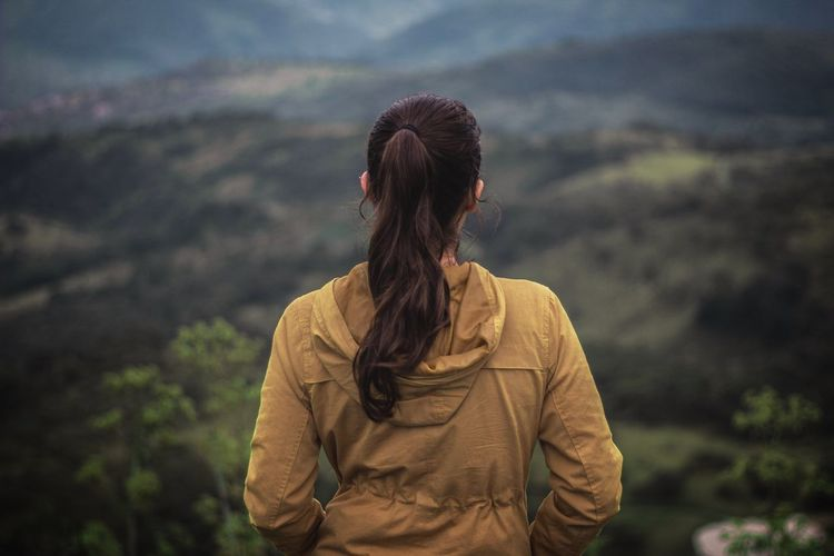 Rear view of woman standing against mountain